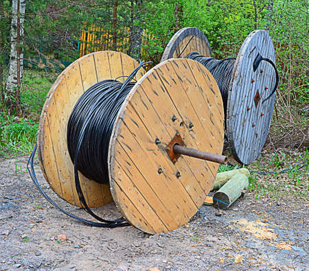 two wooden reels wound by an electric cable