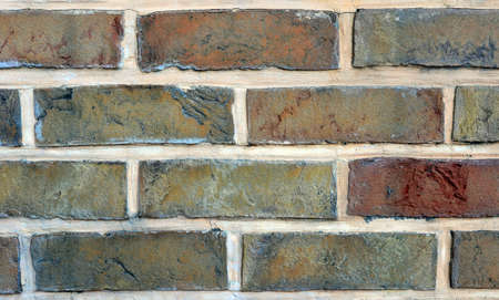 fragment of a brick wall from multi-colored bricks fastened with light solution
