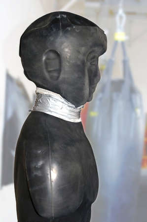 Worn sports black dummy for martial arts with the tied-up neck in a gym