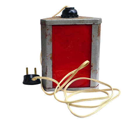 Old worn laboratory red lamp on a white background, with spots of developer and a fixer, corrosion on the case, and the plastic wire which turned yellow from time. Such lamps were used for work with photosensitive photographic materials earlier. Standard-Bild