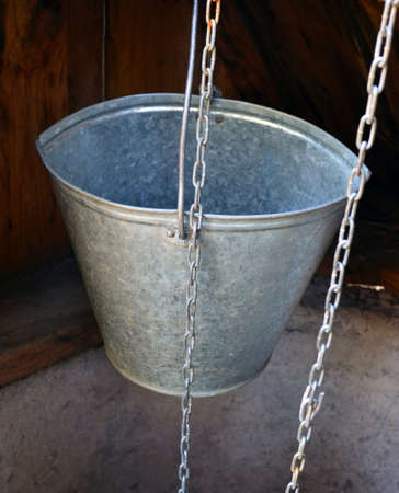 the aluminum bucket hanging on on a chain, in mine of an old well