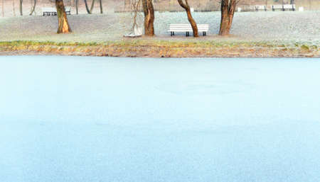 Frosts in the city park. View from the side of the pond. Ice on water and hoarfrost on the shore. Standard-Bild