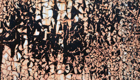 Detail of a wall of rusty sheet metal with peeling brownish rust light paint.