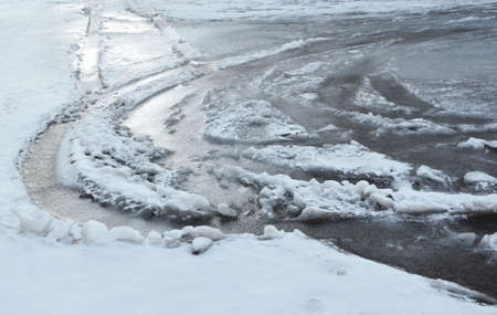 The frozen thawed snow in traces of wheels of cars. The image can be also used as a background. Standard-Bild