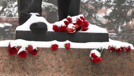 Feet of a bronze monument on a granite pedestal with red roses and carnations in the winter Standard-Bild