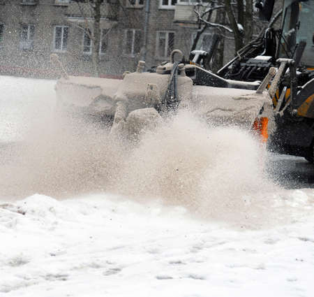 The rotating brush of the snowplow raises a cloud mixed snow and sand during cleaning of the street