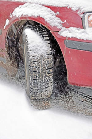 Winter automobile tire on wheel of red car which stopped recently. Heavy snowfall fast covers up tracks of protectors on road, body and wheel. Standard-Bild