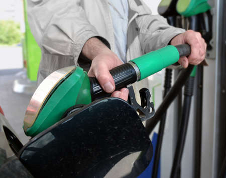 The man's hand with fuel nozzle closeup. He fills tank of car with gasoline at gas station.