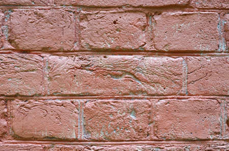 Fragment of brick wall painted pink color. Plaster is partially destroyed by influence of time and environment. Abstract background. Texture.