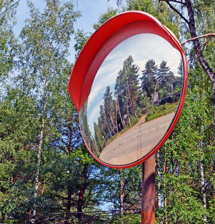 Security mirror thereflecting twisting highway in rural areas as metaphor of safety on the road
