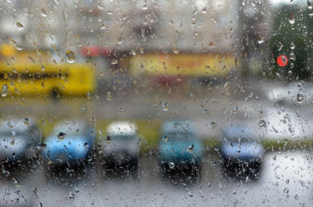City street in rainy weather through glass with water drops. The image can be used as background.