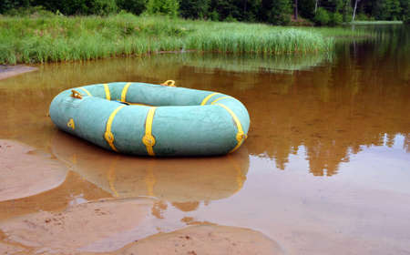 Inflatable boat in shallow water near the sandy coast of the beautiful forest lake