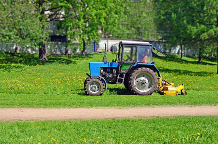 Tractor with mower cutting grass on the lawn Standard-Bild