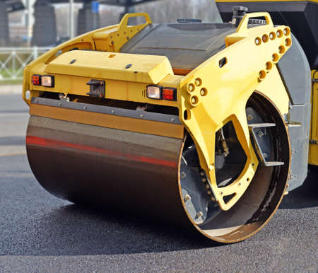 Roll closeup. Fragment of road roller that compacts fresh asphalt on pavement Standard-Bild