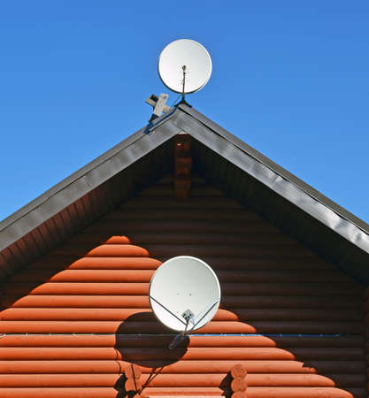 Two TV satellite dishes on wall and roof of wooden log house against of blue sky