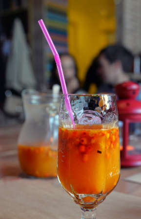 Bright orange sea buckthorn juice in glass with drinking tube in cozy cafe