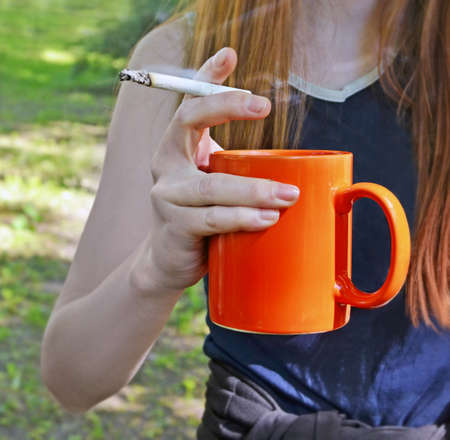 Hand of the young thin pale woman with the smoking cigarette and a cup of coffee as a metaphor of addictions and dependences Standard-Bild