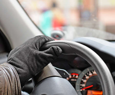 Male hand in suede glove on steering wheel closeup. Driving.