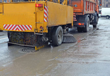 Road cleaning using a sweeper towed bya truck in rainy weather