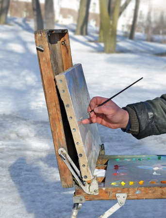 Hand of senior artist painting picture from life in open-air in winter or early spring. Canvas and palette with paints are located on old wooden easel.