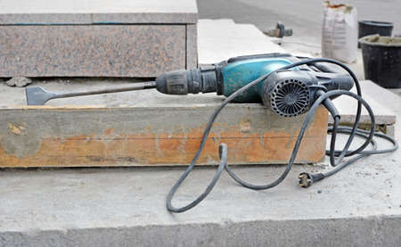 Electric rotary hammer drill bit on unfinished ladder steps