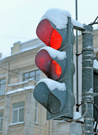 Road traffic light with red in winter in twilight during snowfall in city