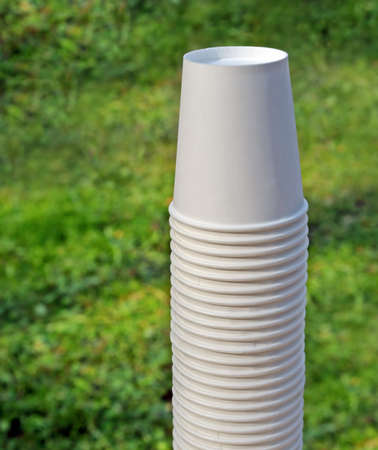 Stack of disposable paper cups against of blur lawn Standard-Bild