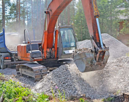 Construction in countryside. Excavator scoops gravel from large pile with bucket to pour it into truck body. Standard-Bild