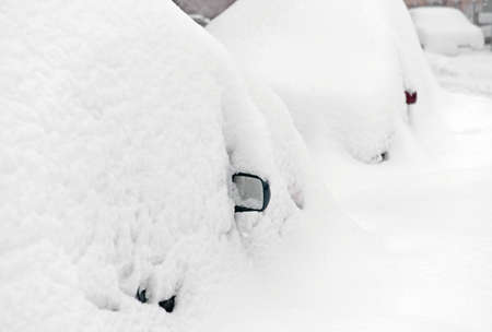 Parking during heavy snowfall. Vehicles are similar to large snowdrifts. Abstract background. Focus on rear view mirror of nearest car