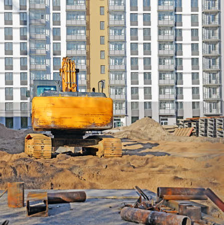 Construction site. Focus on caterpillar excavator that stands on pile of sand among pipes and concrete blocks in front of unfinished building.