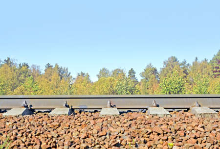 Rails on railway embankment in forest against of the and tops of trees. Side view. Background. Standard-Bild