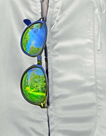 Sunglasses hang on zipper of white jacket . Lenses and frame reflect blur bright spring landscape. Standard-Bild