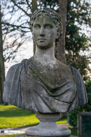 greco roman: A Roman Grecian bust in the grounds of a country house Stock Photo