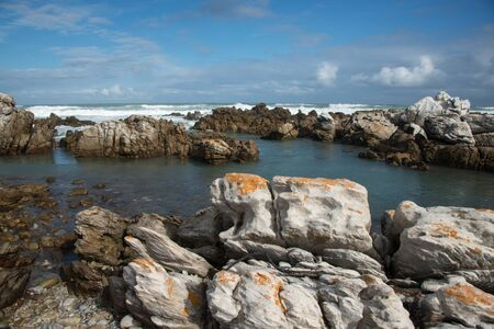 breaking in: Rocks in the sea at Cape Agulhas with waves breaking in the background Stock Photo