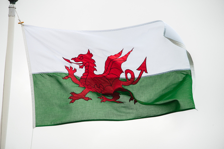 bandera de gales: The Welsh flag against a cloudy sky