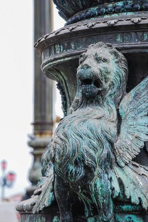 winged lion: Un le�n con alas tallado en una farola en Venecia, Italia