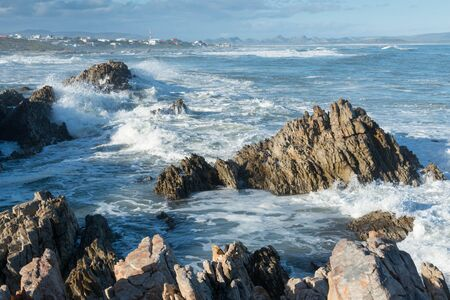 Waves crash on rocks in the fishing village of Kleinbaai, near Gansbaai, South Africa Stock Photo