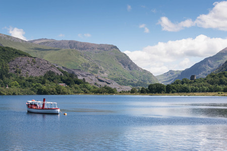 A boat on the tranquil blue waters of Llyn padarn, a naturally formed lake in Snowdonia, north Wales Imagens