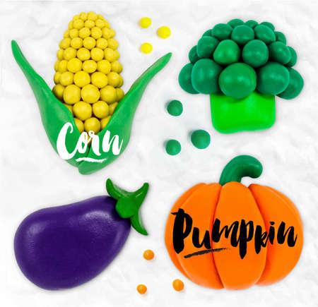 modeling: Plasticine modeling vegetables pumpkin corn  broccoli eggplant cobbled together on a white plasticine background