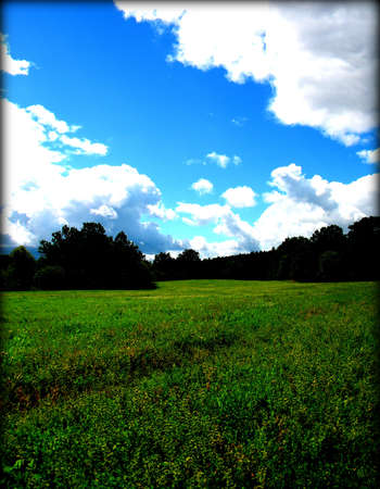 a blue and cloudy sky over farmland Stock Photo