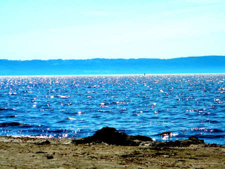 blue shining sea with mountains in the background