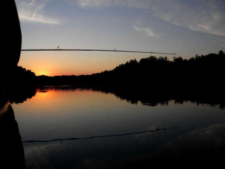 a fishing rod and a boat at sunset