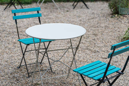 Two blue wooden folding chairs and a round white table are standing on gravel in the backyard of a cafe in natural light in the evening Banco de Imagens