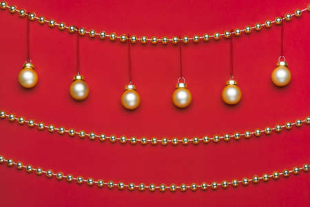 Six small matte golden-coloured Christmas ornament hanging on a row decorated by shiny golden-coloured Christmas beads wreath on red background in studio light