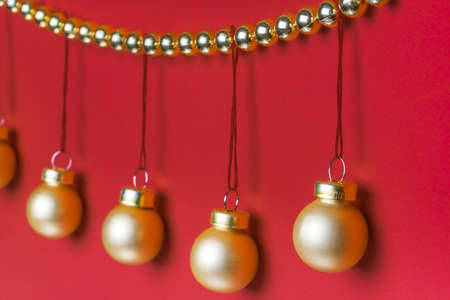 Five small matte golden-coloured Christmas ornament hanging on a row decorated by shiny golden-coloured Christmas beads wreath on red background in studio light