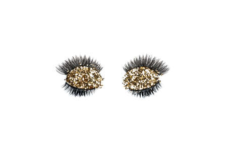 Dramatic black long false eyelashes decorated with bright sparkling golden glitter isolated on white background shot with studio light