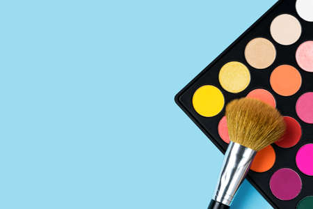 Black plastic palette of brightly coloured yellow, red, pink, orange eyeshadow and a large make-up brush laying on top of the palette arranged in the corner of pastel baby blue background shot with studio light from above