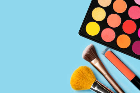Black plastic palette of brightly coloured yellow, red, pink, orange eyeshadow, orange liquid lipgloss, and two make-up brushes arranged in the corner of pastel baby blue background shot with studio light from above Stock Photo