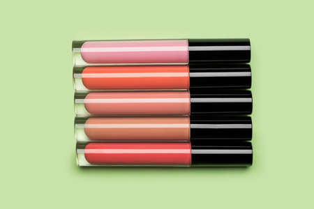 Five brightly coloured bottles of liquid lipstick and lip gloss arranged in a row on clean pastel green background shot with studio light from above