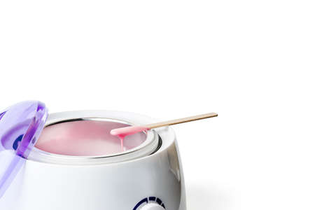Close-up of wax heater with hot pink wax and a wooden spatula